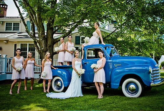 Bride and bridesmaids around blue vintage truck
