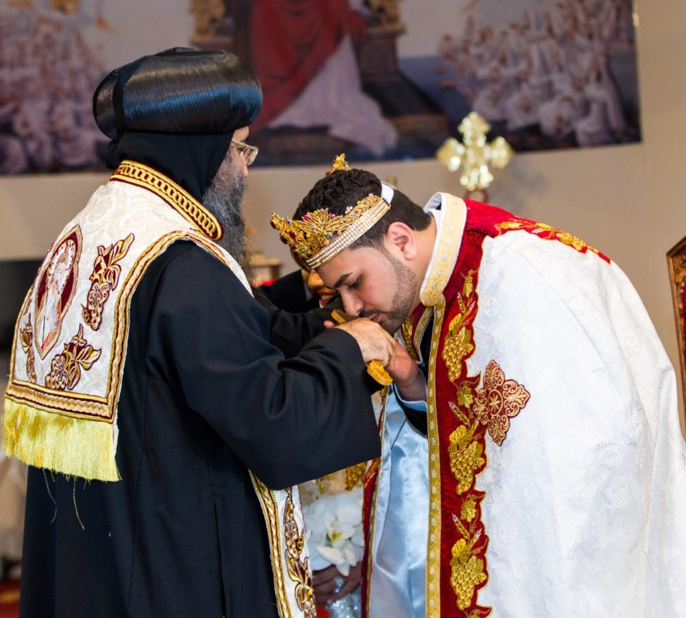 Broom kisses coptic priest hand